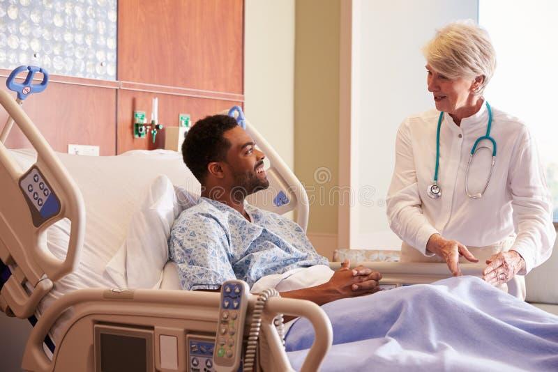Paciente fêmea do doutor Talking To Male na cama de hospital imagem de stock royalty free