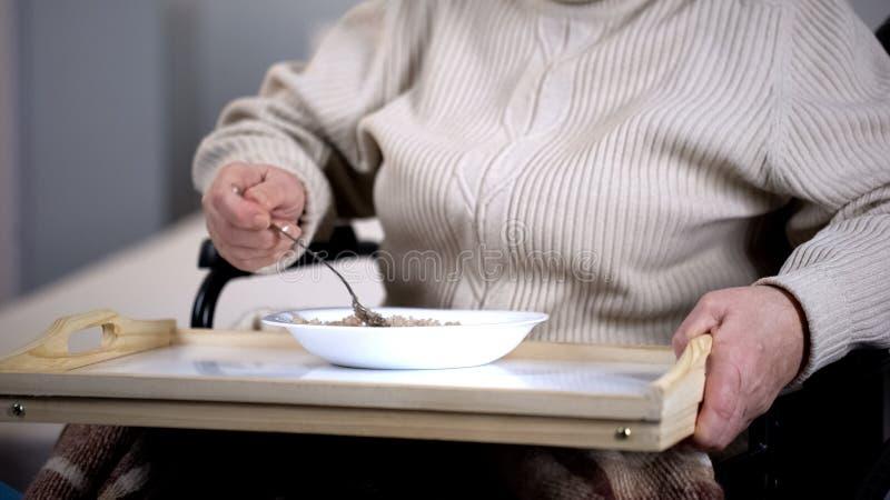 Paciente fêmea envelhecido que come o papa de aveia, cuidados médicos no hospital, lar de idosos fotografia de stock