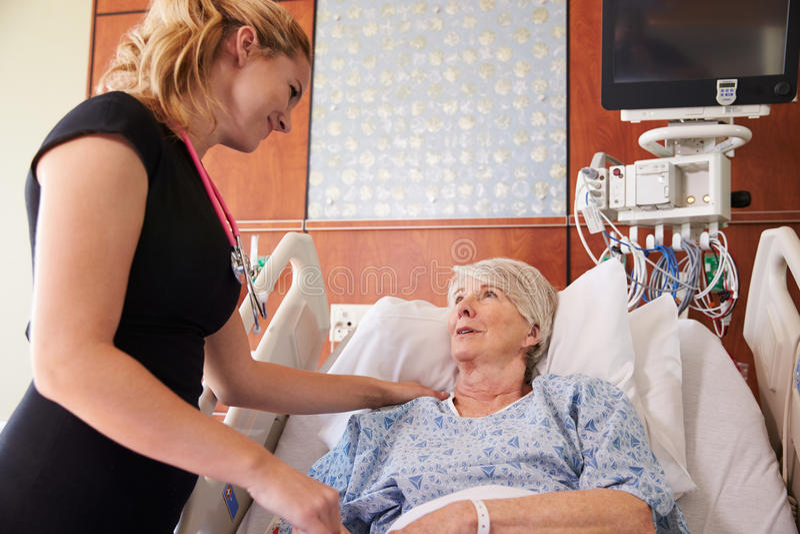 Paciente fêmea fêmea do doutor Talks To Senior na cama de hospital imagens de stock