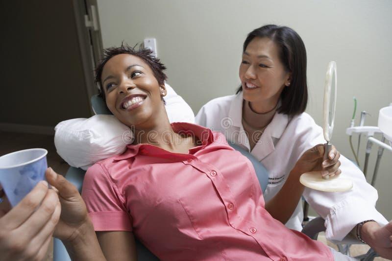 Paciente fêmea feliz na clínica do dentista imagem de stock royalty free