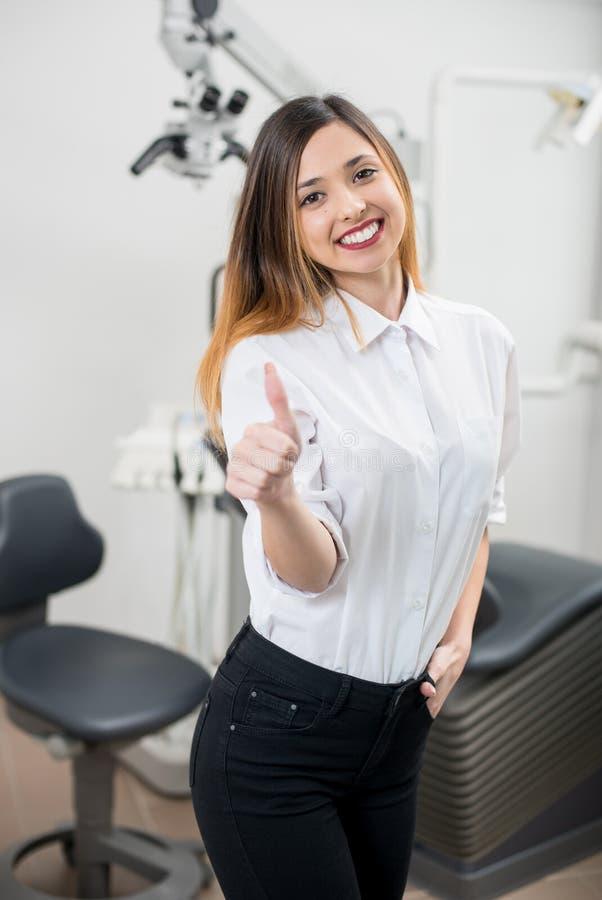 Paciente fêmea feliz novo com os dentes brancos perfeitos que mostram os polegares acima após o tratamento na clínica dental mode fotografia de stock