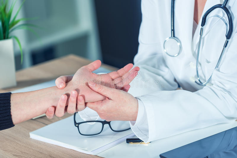 Paciente fêmea no exame médico do doutor ortopédico para o injur do pulso foto de stock