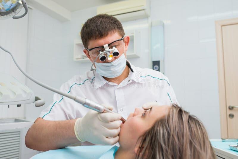 Paciente fêmea novo que recebe o tratamento dental de um dentista foto de stock