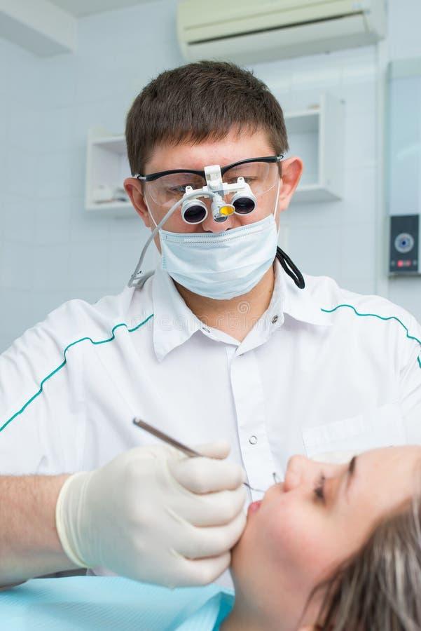 Paciente fêmea novo que recebe o tratamento dental de um dentista fotografia de stock royalty free