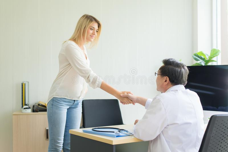 Paciente feliz y sonriente de la mujer que da el apretón de manos para servir al doctor en el hospital fotografía de archivo libre de regalías