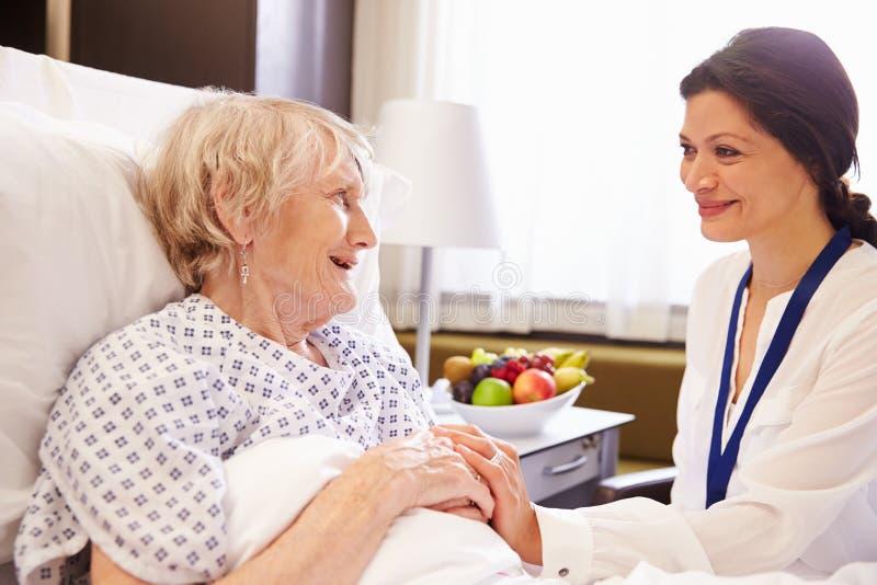 Paciente femenino del doctor Talking To Senior en cama de hospital fotografía de archivo