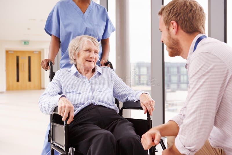 Paciente femenino del doctor Talking To Senior en silla de ruedas fotos de archivo libres de regalías