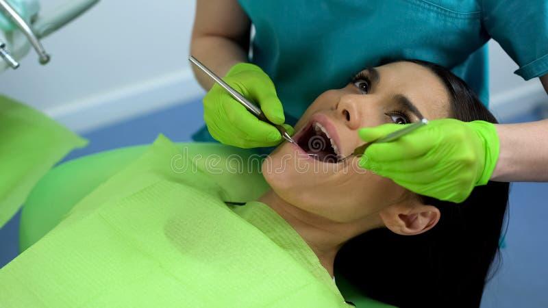Paciente femenino en el chequeo rutinario en la clínica dental moderna, dientes sanos fotos de archivo libres de regalías