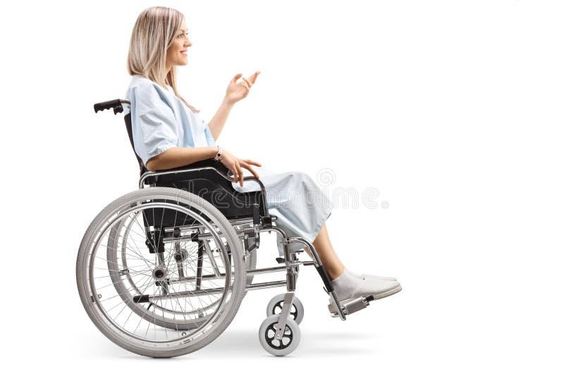 Paciente femenino joven en una silla de ruedas que gesticula con su mano fotografía de archivo libre de regalías