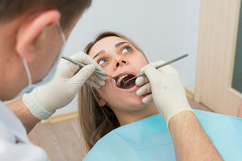 Paciente femenino joven que recibe cuidado dental de un dentista imagenes de archivo