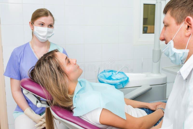 Paciente femenino joven que recibe cuidado dental de un dentista fotos de archivo