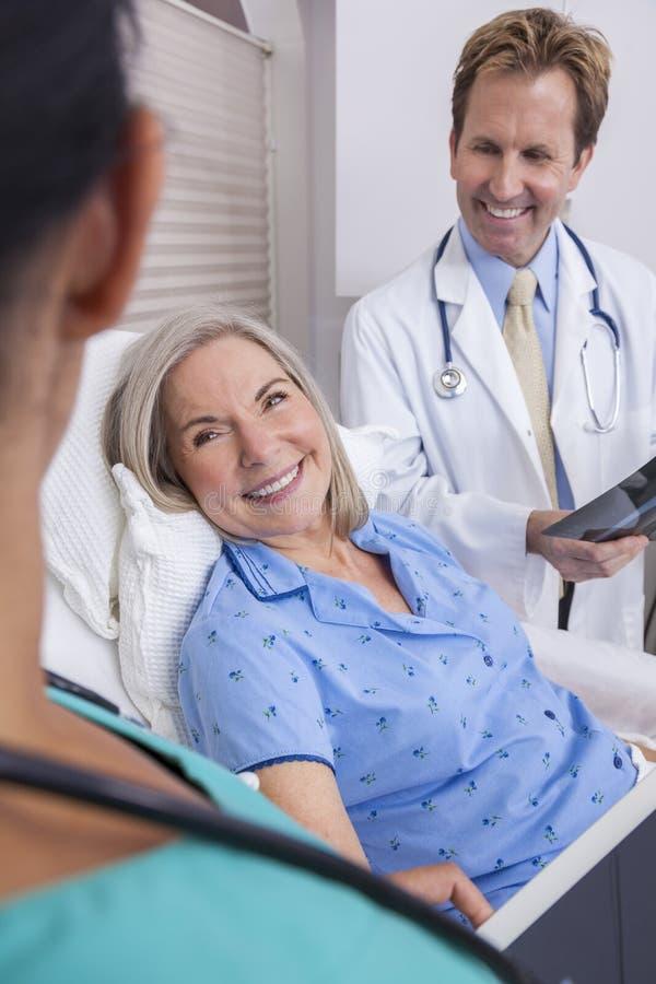 Paciente femenino mayor con el doctor de la enfermera y del varón fotografía de archivo
