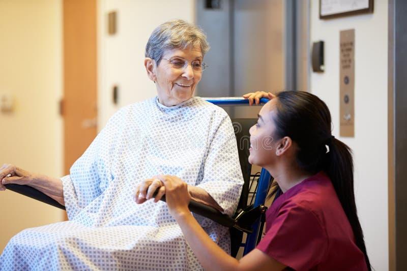 Paciente femenino mayor que es empujado hacia adentro silla de ruedas por la enfermera imagen de archivo