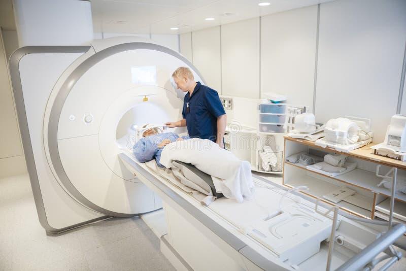 ` Paciente femenino s MRI que experimenta principal de Putting Coil On del radiólogo imagen de archivo