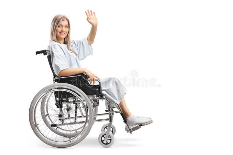 Paciente femenino sonriente en una silla de ruedas que agita en la cámara imagenes de archivo