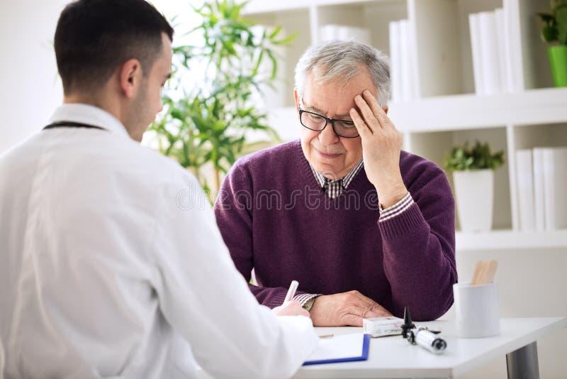 Paciente idoso com dores na necessidade principal que examina imagem de stock