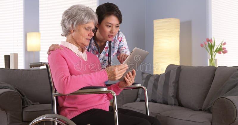 Paciente idoso e enfermeira asiática que têm o divertimento com tabuleta fotografia de stock royalty free