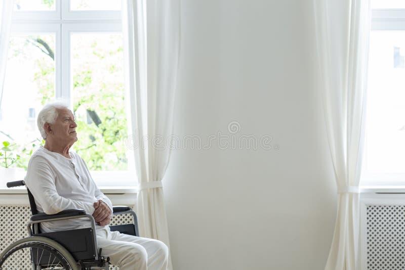 Paciente idoso só em uma cadeira de rodas em uma sala branca ao lado de uma parede vazia Coloque seu logotipo fotos de stock royalty free