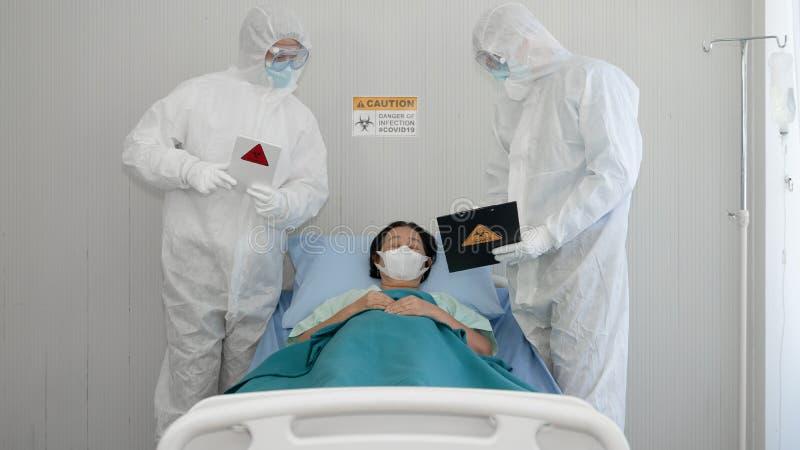 Paciente infectado con coronavirus en cama con peritos de control de la enfermedad revisando el estado del paciente en la sala de fotos de archivo