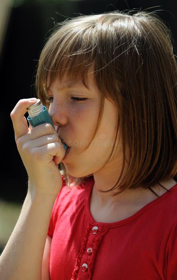 Paciente joven del asma que usa un inhalador imágenes de archivo libres de regalías