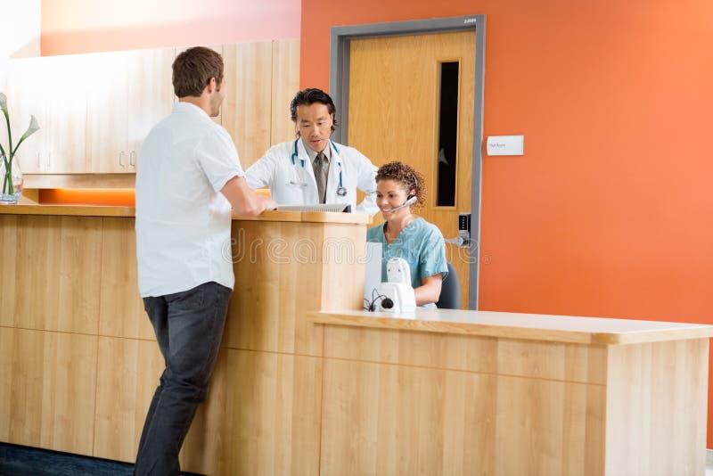 Paciente médico de Team Working At Reception While fotografia de stock royalty free