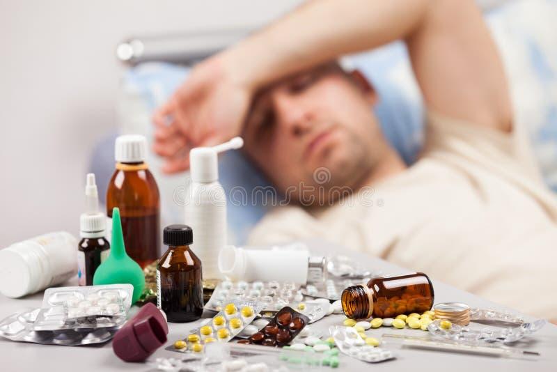 Paciente mal del hombre que miente abajo cama fotografía de archivo
