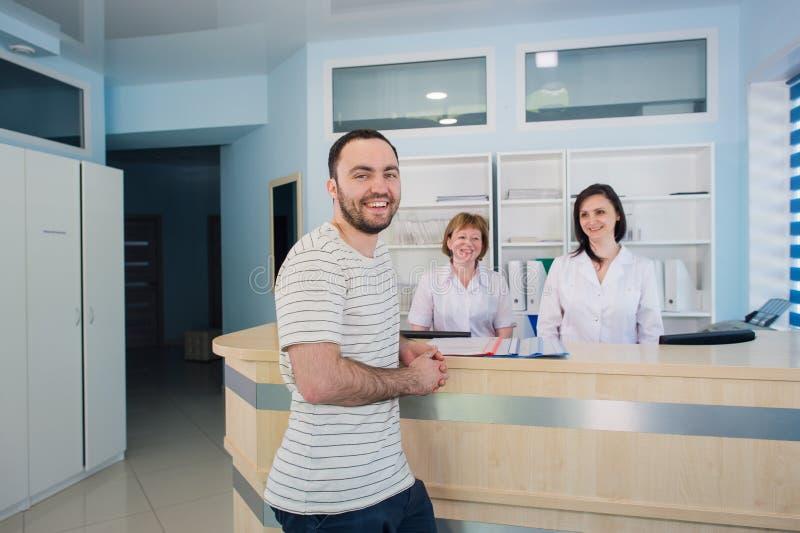 Paciente masculino con el doctor y la enfermera en el mostrador de recepción en hospital imagen de archivo libre de regalías