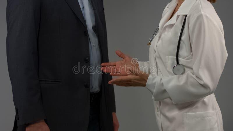 Paciente masculino de consulta do doutor da mulher, diagnóstico de fala, recomendando medicamento imagem de stock