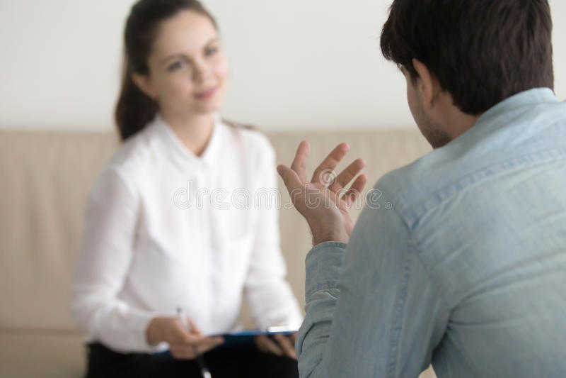 Paciente masculino de consulta do psicólogo fêmea, entrevista de trabalho, busi imagem de stock royalty free