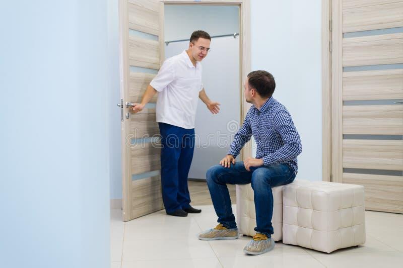 Paciente masculino de invitación del doctor de sexo masculino a su oficina imagen de archivo libre de regalías