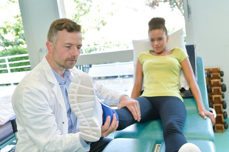 Paciente masculino de la pierna de la prueba del fisioterapeuta en sitio fisio fotografía de archivo