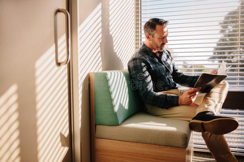 Paciente masculino en la sala de espera del doctor fotos de archivo
