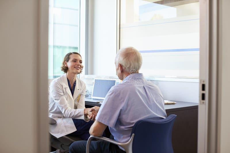 Paciente masculino maduro del doctor Shaking Hands With en oficina imagenes de archivo