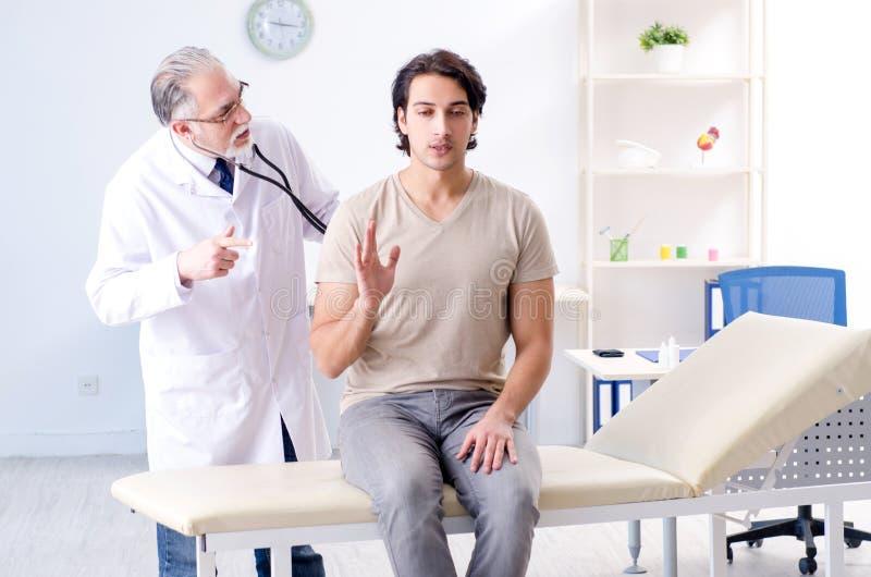 Paciente masculino novo que visita o doutor idoso fotografia de stock royalty free