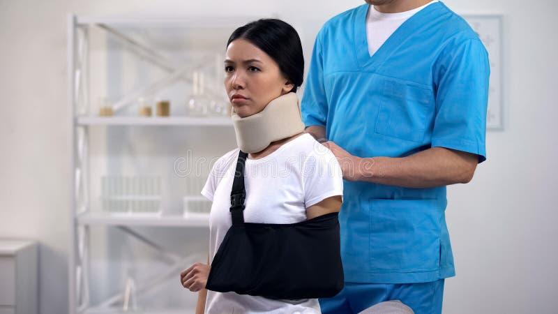 Paciente masculino profissional da virada do estilingue do braço da fixação do cirurgião no colar cervical da espuma foto de stock royalty free