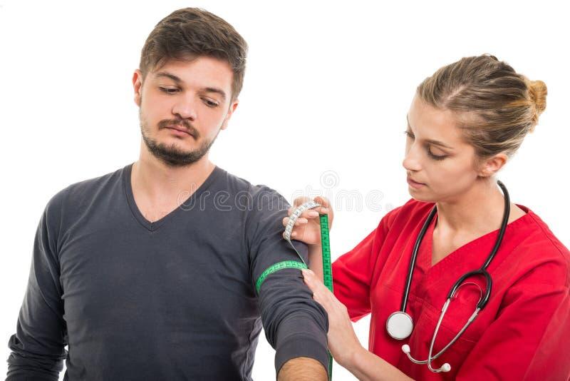 Paciente masculino que está sendo medido pelo doutor fêmea bonito imagens de stock