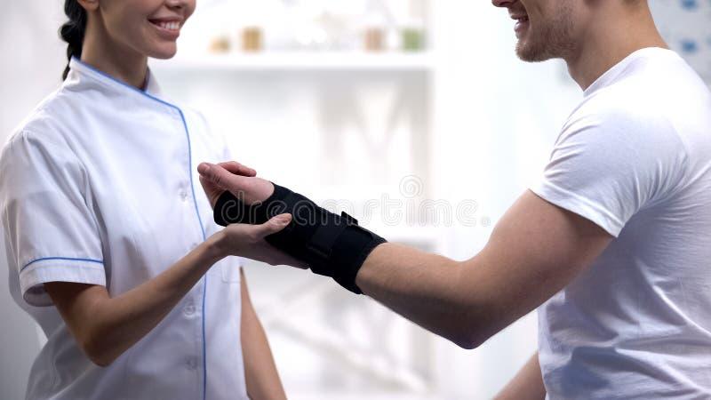 Paciente masculino satisfeito profissional do apoio de pulso da fixação do ortopedista, cuidados médicos imagens de stock royalty free