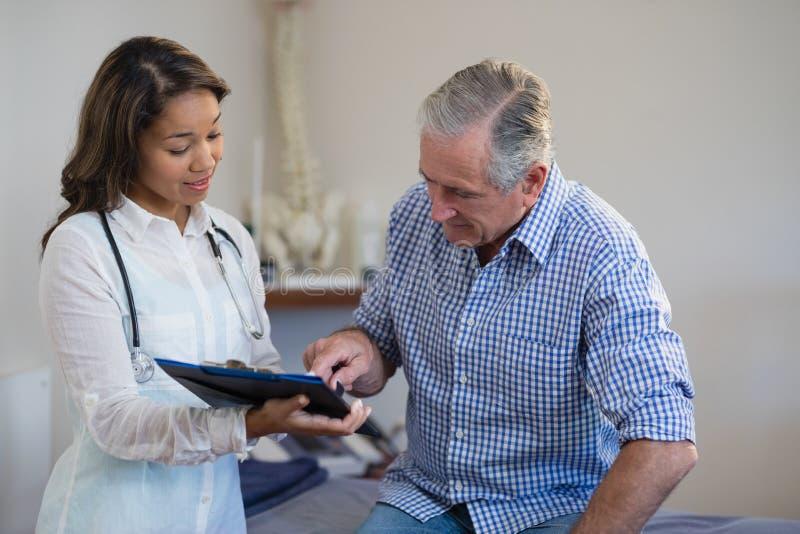 Paciente masculino superior que aponta no arquivo ao discutir com o terapeuta fêmea imagem de stock royalty free