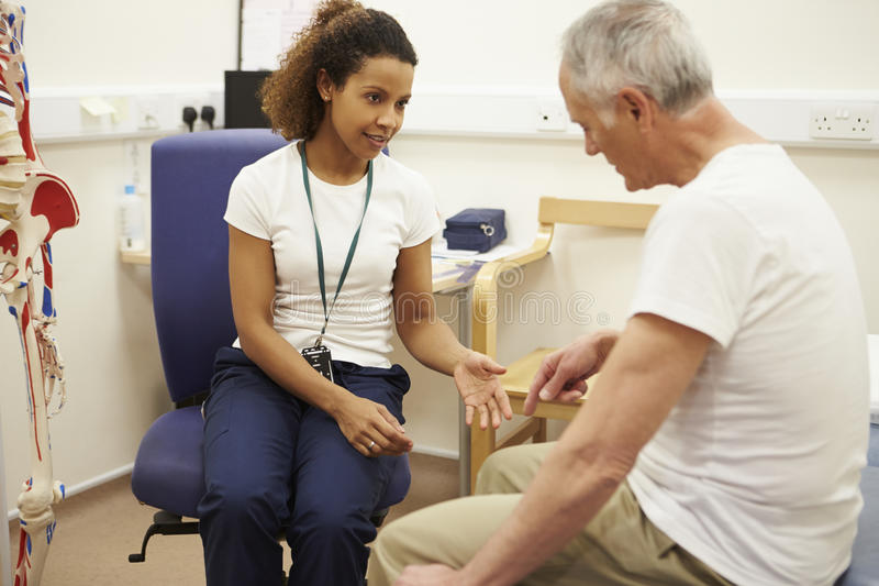 Paciente masculino superior que tem a fisioterapia no hospital foto de stock royalty free