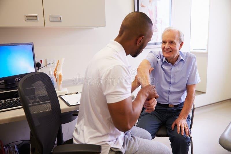 Paciente masculino superior que trabalha com fisioterapeuta In Hospital imagem de stock