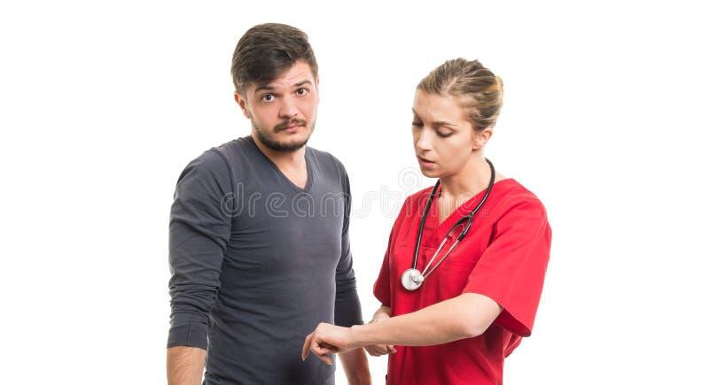 Paciente masculino y doctor de sexo femenino que muestran siendo último gesto foto de archivo