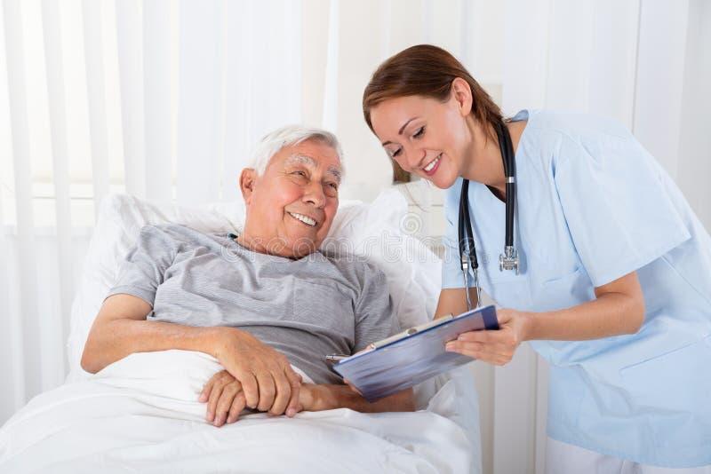 Paciente mayor de With Clipboard Visiting de la enfermera imagen de archivo libre de regalías