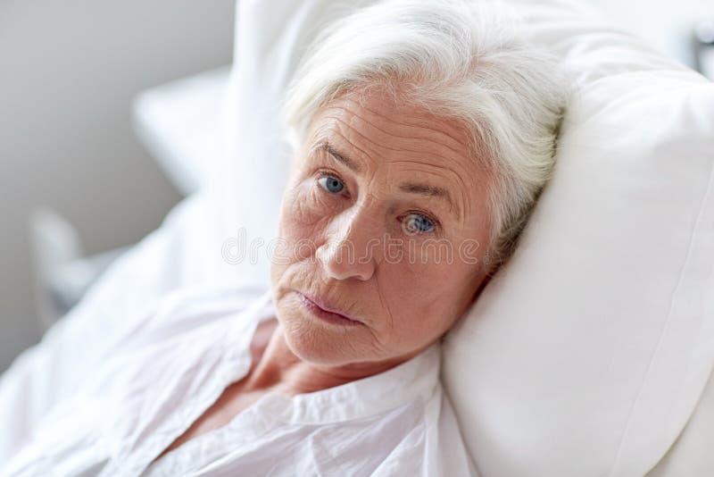 Paciente mayor de la mujer que miente en cama en la sala de hospital fotografía de archivo