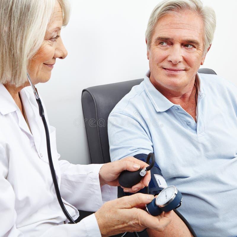 Paciente mayor en la medida de la presión arterial fotos de archivo