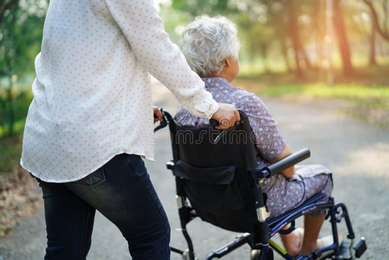 Paciente mayor o mayor asi?tico de la mujer de la se?ora mayor con cuidado, ayuda y ayuda en la silla de ruedas en parque en d?a  imagen de archivo libre de regalías