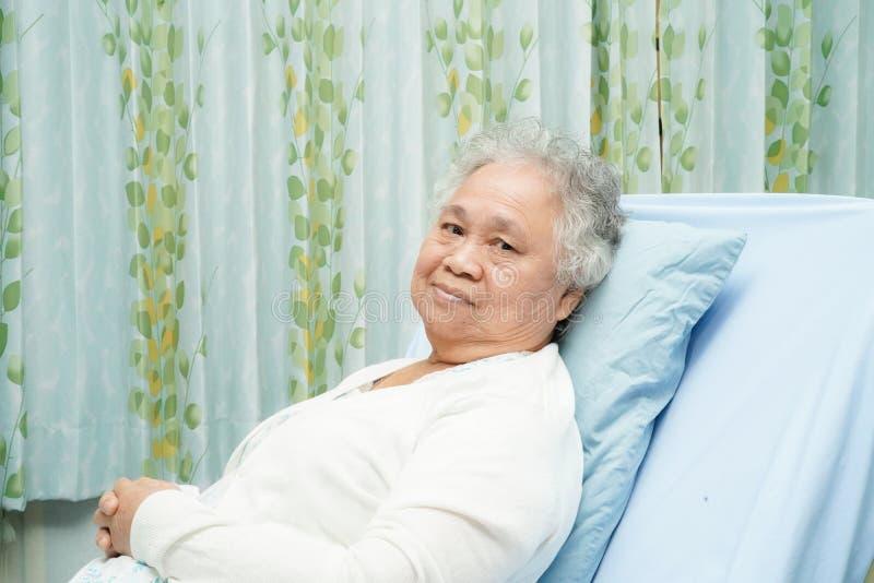 Paciente mayor o mayor asi?tico de la mujer de la se?ora mayor que se sienta en cama en sala de hospital de cuidado con esperanza imagenes de archivo
