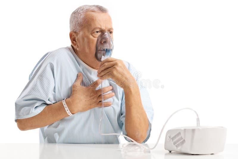 Paciente mayor que tiene dolor de pecho y que usa un inhalador fotografía de archivo libre de regalías