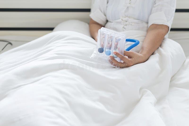 Paciente mayor que usa el espirómetro incentivo o tres bolas para estimular los pulmones en dormitorio imagenes de archivo