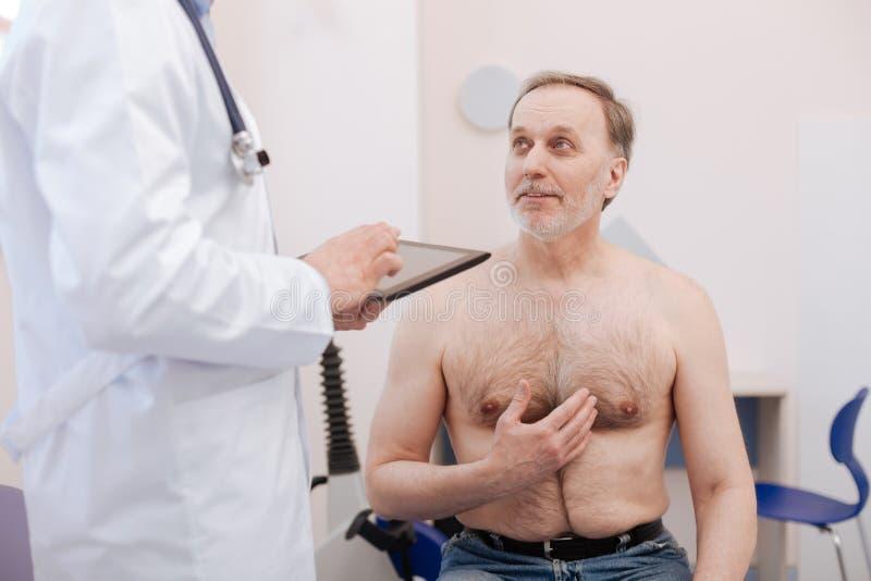 Paciente mayor sorprendido que explica algo imágenes de archivo libres de regalías
