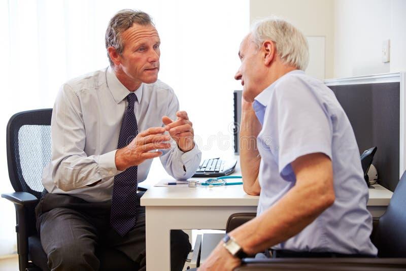Paciente mayor teniendo consulta con el doctor In Office foto de archivo libre de regalías